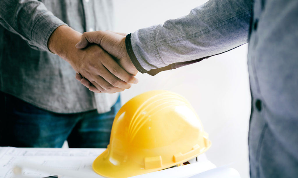 Construction worker greeting a foreman at renovating apartment.